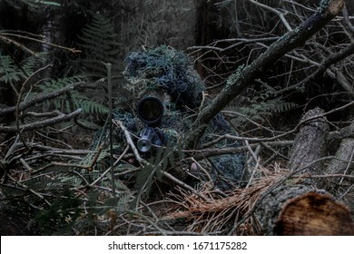 Man in a ghillie suit hidden in the forrest, aiming through a scope on a rifle. May both represent a sniper or a hunter.