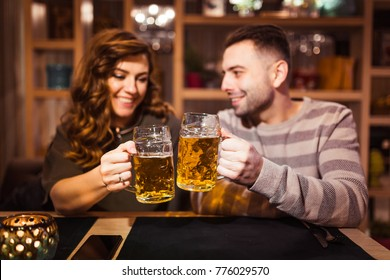 man and girl with beer mugs in a restaurant