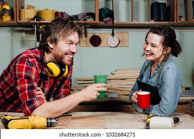 Man and girl carpenters having break from indoor work in wood workshop. Coffee time, drink, share experiences, discuss. Teacher and student. Laughing smile.