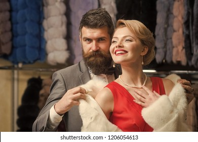 Man and girl with cheerful faces on clothes rack background. Fashion and love concept. Couple in love tries expensive overcoats on. Customer with beard and woman buy furry coat.