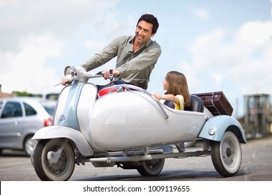 Man with girl driving a scooter