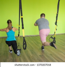 A man and a girl are engaged on the loops of the TRX performing exercises Bulgarian split-squat, strengthening the muscles of the buttocks, legs and quadriceps