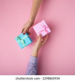 man and girl exchanging gifts from hand to hand,boxes wrapped in decorative paper with a bow on pastel pink background, the concept of holidays and love , top view