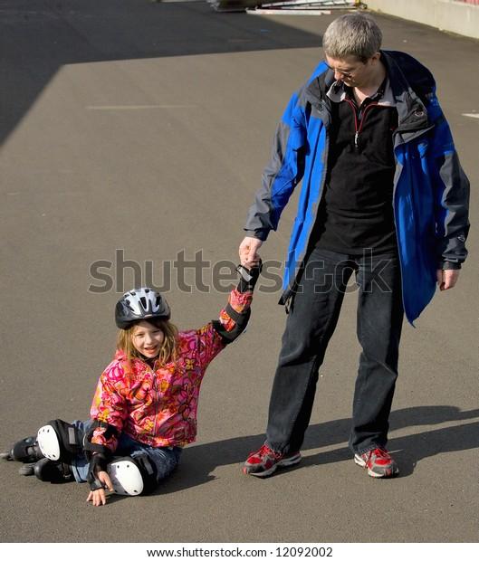 The man with  girl  in a helmet and on roller skates fell on the asphalt