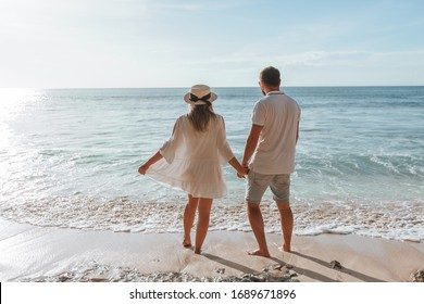 man and a girl hold hands and watch the sunset on the beach