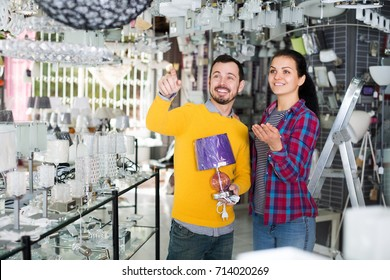 Man with girl in lighter shop points to interesting model lamp