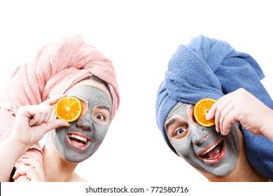 man with girl looks at camera hold orange slices near face mask for skin, guy with girl make a mask for face together, funny couple of lovers, isolated photo, emotional gender role