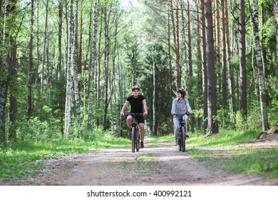 Man and girl on bikes in the forest