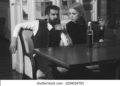 Man and girl sharing bottle of red wine in restaurant. Woman with blond hair and hipster sitting with glasses at table. Couple in love. Date and dating. Alcohol, addictive and convive. Unhealthy habit