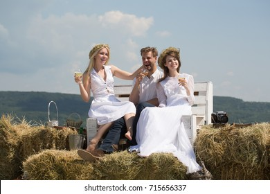 Man and girls drinking champagne on bench. Happy friends enjoying picnic on natural landscape. Women smiling in white dresses. Wine tasting concept. Summer vacation, holidays and celebration