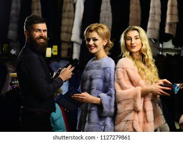 Man and girls with happy faces hold wallets on clothes background. Friends in shop: ladies and gentleman try expensive overcoats on. Customer with beard and women buy furry coats. Rich fashion concept