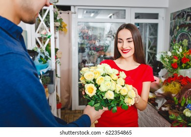 Man gives a beautiful girl in a red bouquet of flowers, in a flower shop