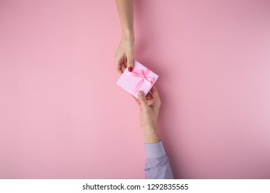 man gives a girl a gift from hand to hand,box wrapped in decorative paper with a bow on a pink pastel background, the concept of holidays, love and relationships, top view