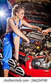 Man gives girl a tool to repair a car, working on the transmission.