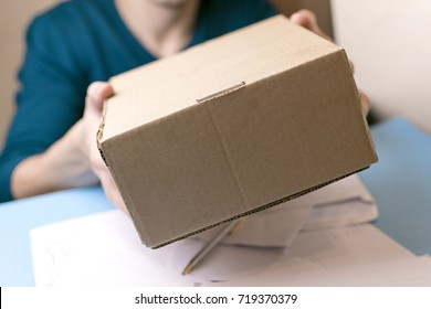 The man gives a parcel to the post office. Mail.