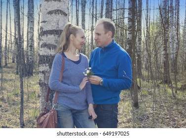 The man gives to the woman a bouquet of snowdrops in a birchwood in the spring, toning