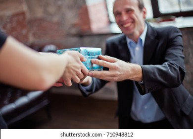 man gives a woman a gift for New Year. Hands of woman receiving gift in blue box. A smiling man gives a Christmas present.