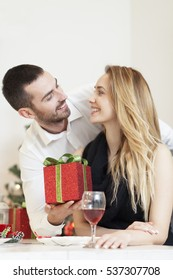 Man gives a woman a gift on Christmas Eve