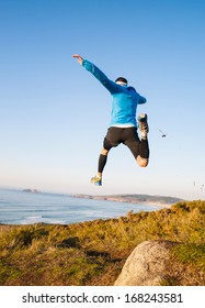 Man giving a big jump while practicing trail running with a coastal landscape in the background.