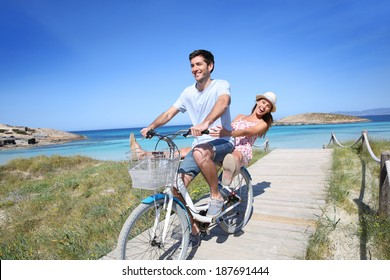 Man giving bike ride to girlfriend on beautiful Island