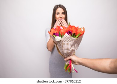 Man giving a bouquet of flowers and surprised woman isolated on white background
