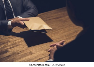 A man giving bribe money in a brown envelope to another businessman in a corruption scam