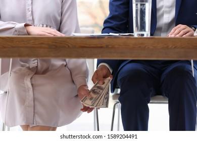 Man giving bribe money under table indoors, closeup