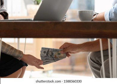 Man giving bribe money to woman under table in office, closeup