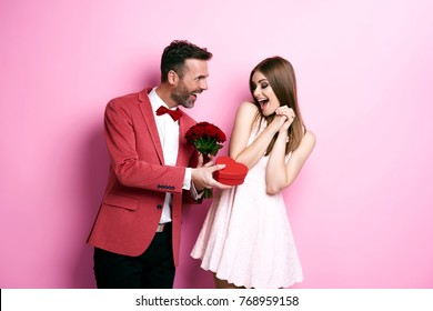Man giving bunch of rose and chocolate box