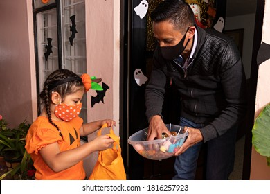 A man giving candies to a girl dressed in a pumpkin costume in the night of halloween