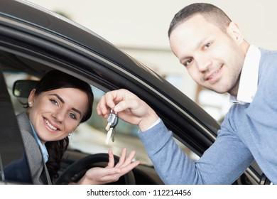 Man giving car keys to a woman thru a window