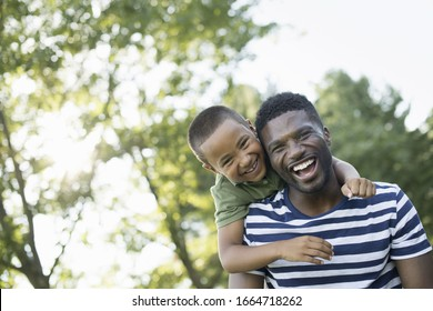 A man giving a child a piggyback, in the shade of trees on a summer day.