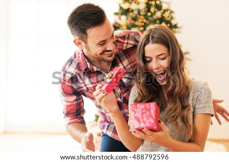 man giving christmas present his girlfriend の写真素材 今すぐ編集