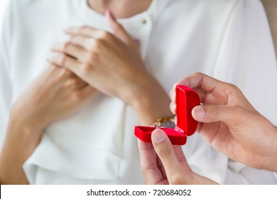 Man giving a diamond ring in a red box to his grilfrend and asking her to marry.