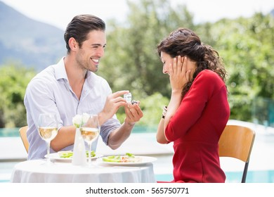 Man giving engagement ring to astonished woman while sitting at poolside