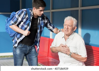 Man giving first aid to senior with heart attack