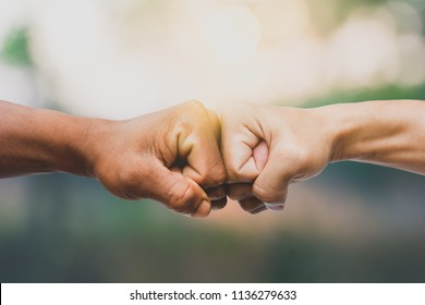 Man giving fist bump in nature background. power of teamwork concept. vintage tone