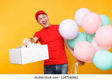 Man giving food order cake box isolated on yellow background. Male employee courier in red cap t-shirt hold colorful air balloons, dessert in empty cardboard box. Delivery service concept. Copy space