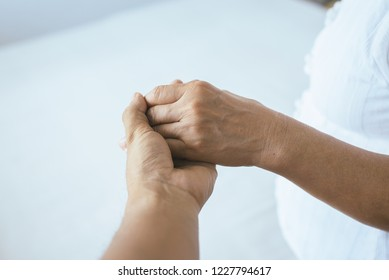 Man giving hand to depressed elderly woman,Psychiatrist holding hands patient,Mental health care concept,Reliable person