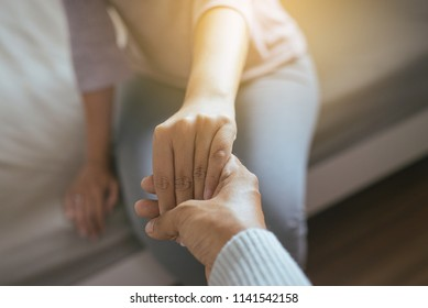 Man giving hand to depressed woman,Psychiatrist holding hands patient,Mental health care concept
