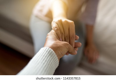 Man giving hand to depressed woman,Psychiatrist holding hands patient,Mental health care concept,Sincere feelings