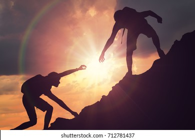 Man is giving helping hand. Silhouettes of people climbing on mountain at sunset.