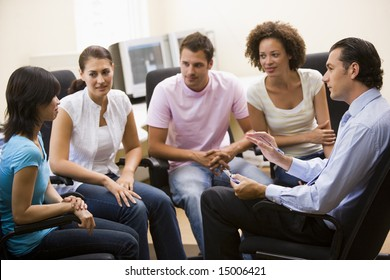 Man giving lecture to four people in computer room