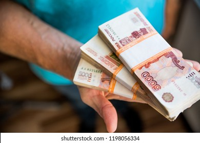 man giving money, Russian Ruble banknotes, over his desk in a dark office - bribery and corruption concept.russian rubles banknotes. Financial theme.stack of banknotes in a man's hand