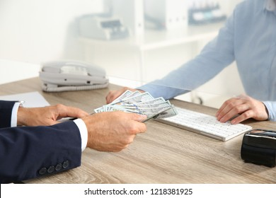 Man giving money to teller at cash department window, closeup