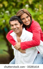 Man giving a piggyback ride to his wife outdoors