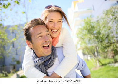 Man giving piggyback ride to woman in town