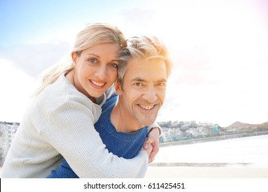 Man giving piggyback ride to woman at the beach