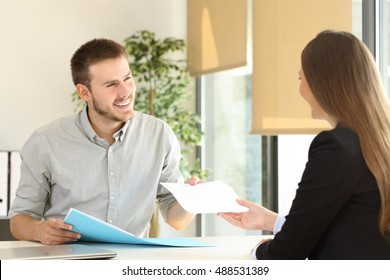 Man giving a resume to the interviewer in a job interview in a desktop at office