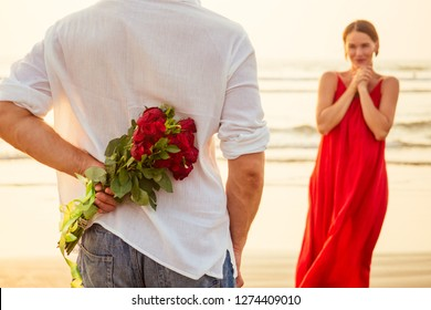 man giving roses to his surprise and wonder woman on the ocean beach. romantic date or wedding or valentines day concept by sea.loving couple celebrating March 8 Women's Day and happy birthday